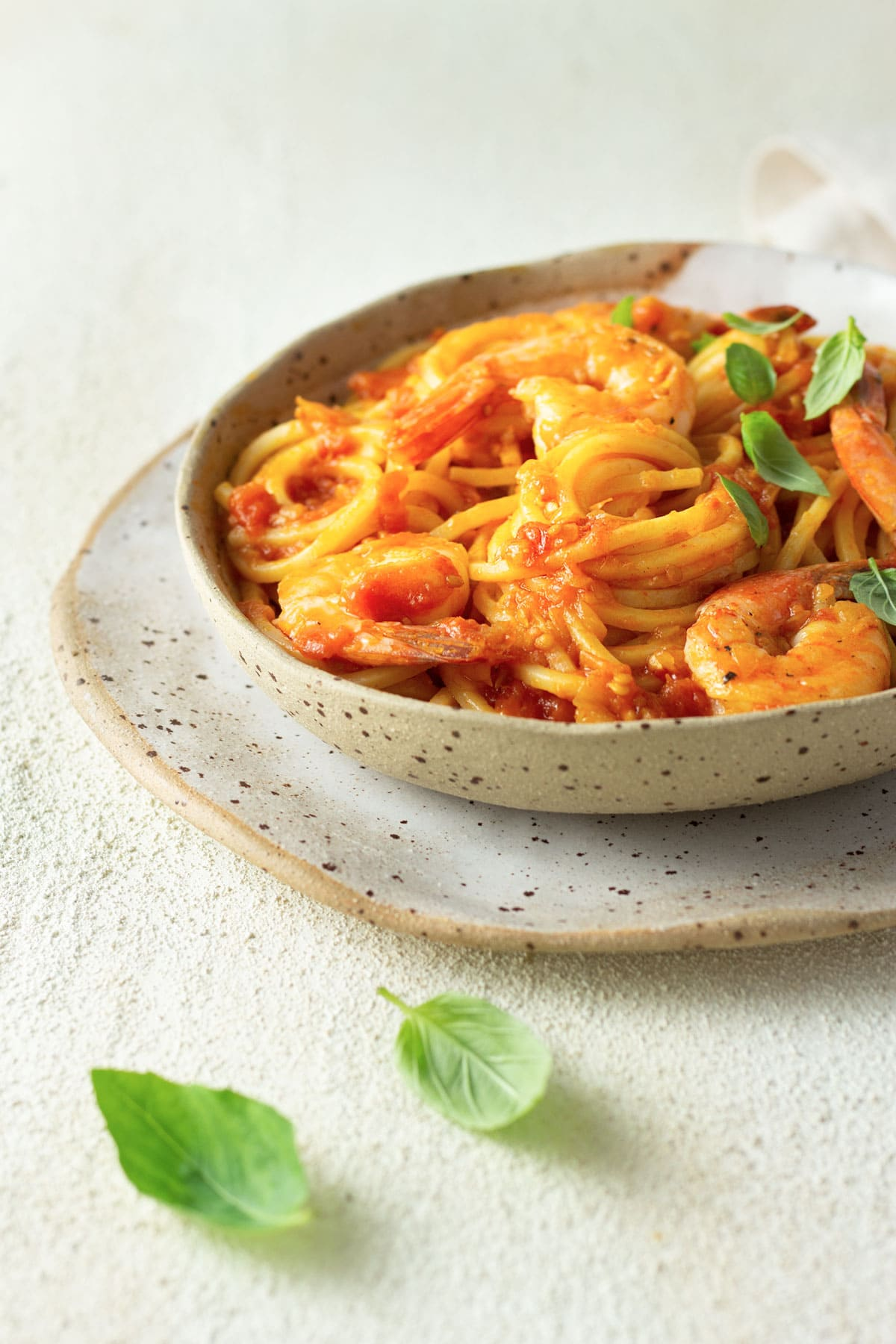 Slightly angled view of a bowl of spaghetti and shrimp with fresh tomato sauce.
