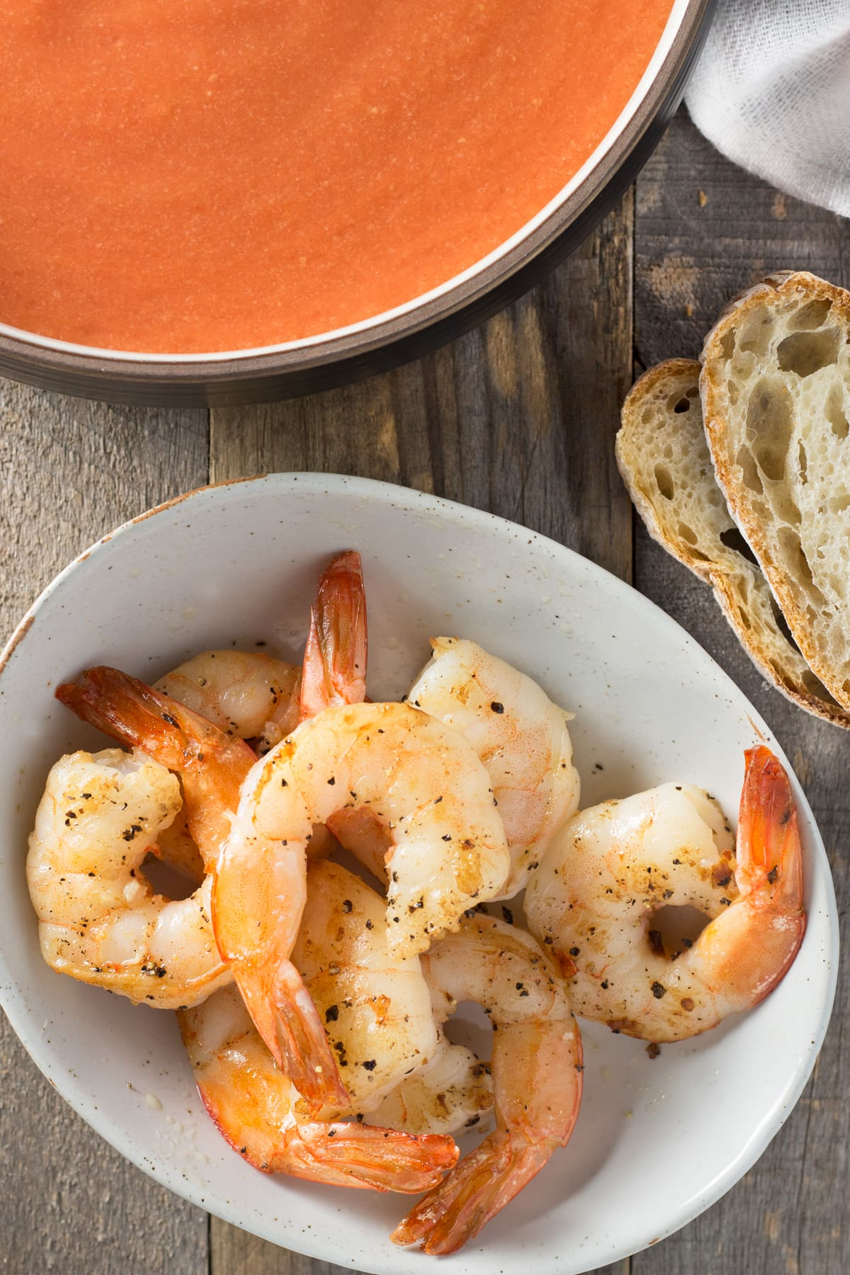 Sautéed shrimp in a bowl next to bread and tomato soup.