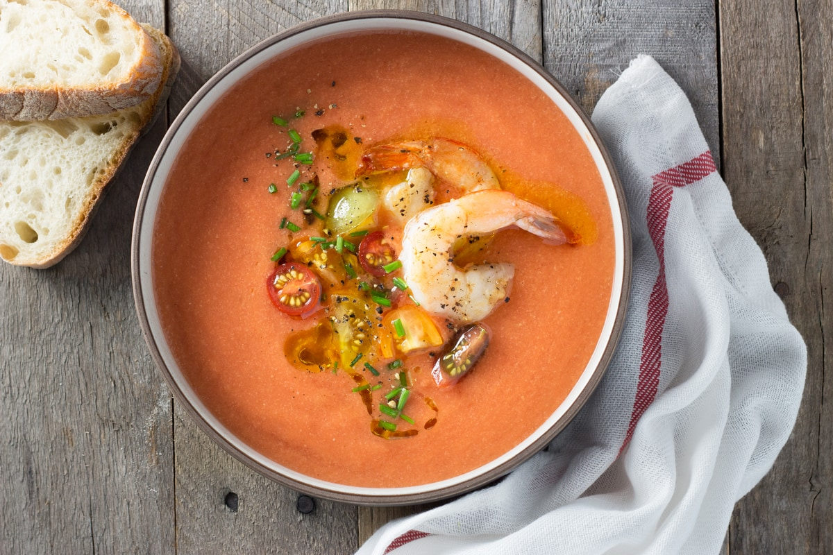 Overhead view of a bowl of tomato gazpacho topped with shrimp, sliced tomatoes and chives surrounded by slices of bread and a dish towel.