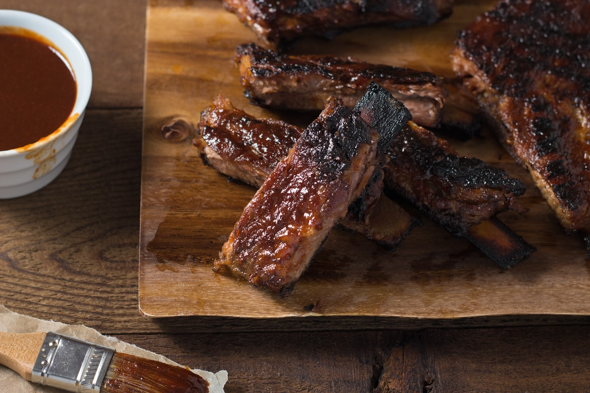 Korean BBQ Pork Ribs on a wood cutting board next to a bowl of barbecue sauce.