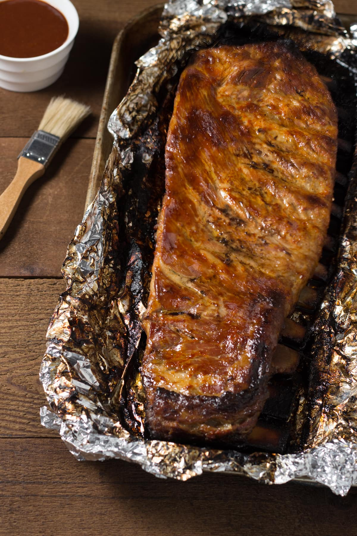 Rack of pork spare ribs in foil on a sheet tray brushed with barbecue sauce.