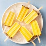 Overhead view of a group of Mango Lassi Popsicles on a plate of ice on a blue surface.
