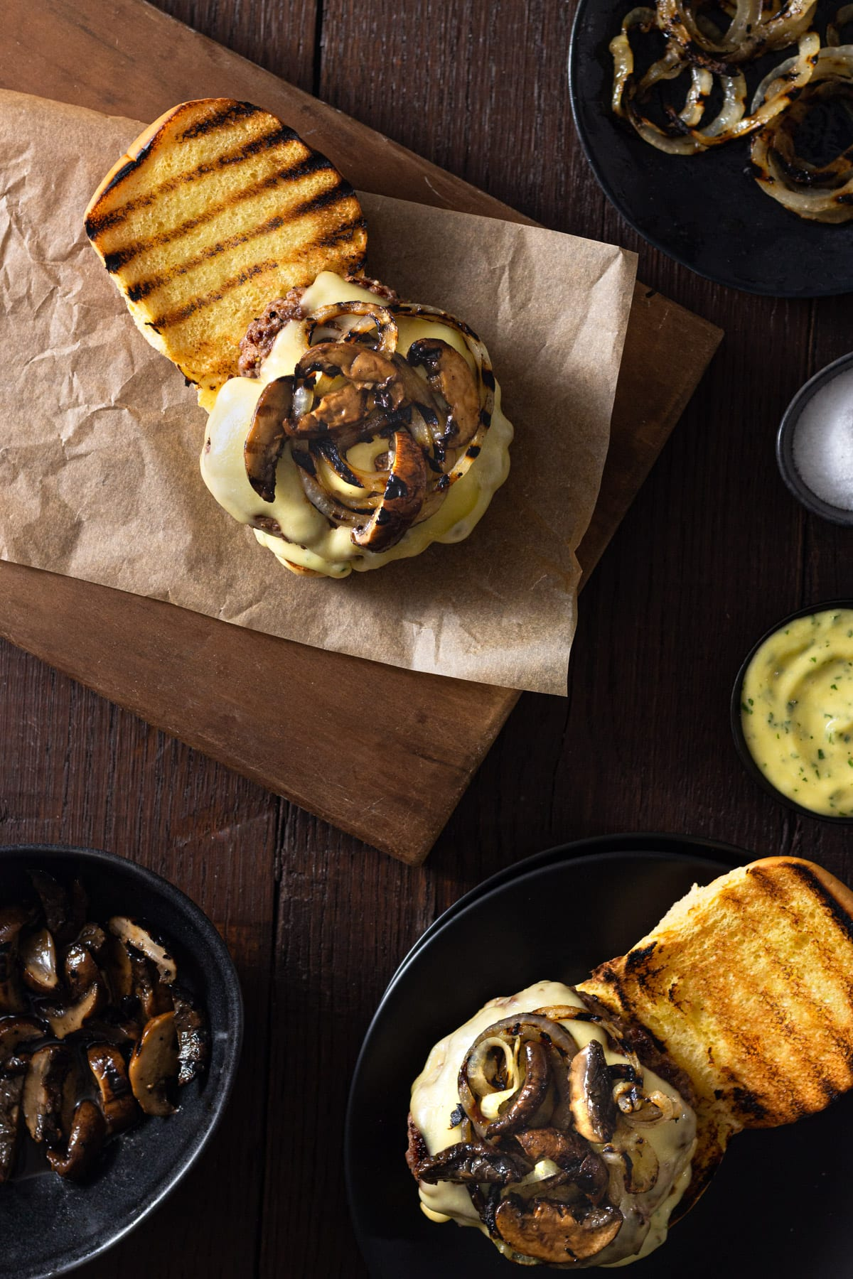Overhead view of two mushroom burgers with bowls of toppings surrounding them on a dark grey surface.
