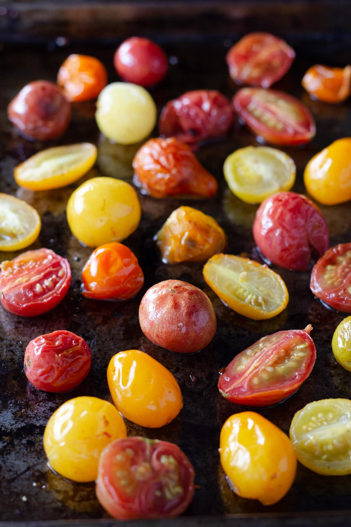 Roasted heirloom, grape tomatoes on a sheet tray.