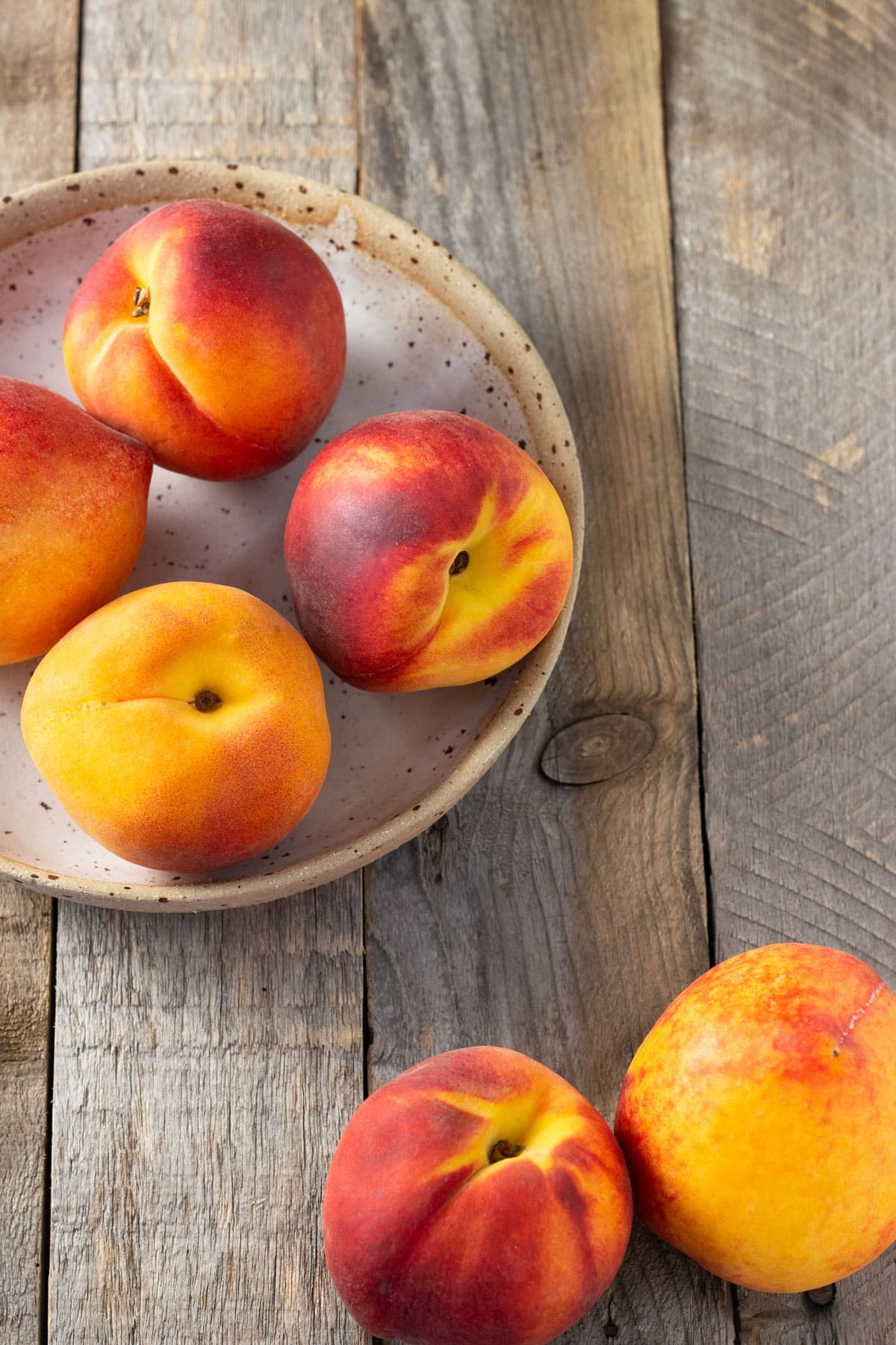 Group of fresh peaches on a rustic wood surface.