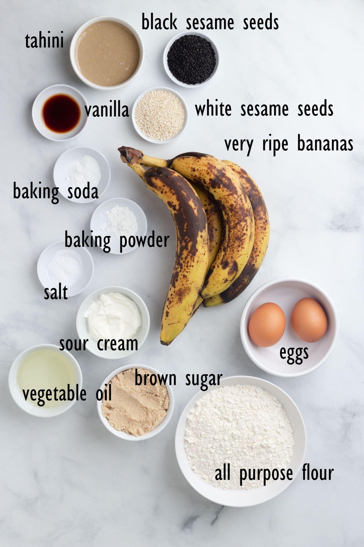 Banana Bread Ingredients including bananas, black and white sesame seeds, tahini, flour, brown sugar and eggs.