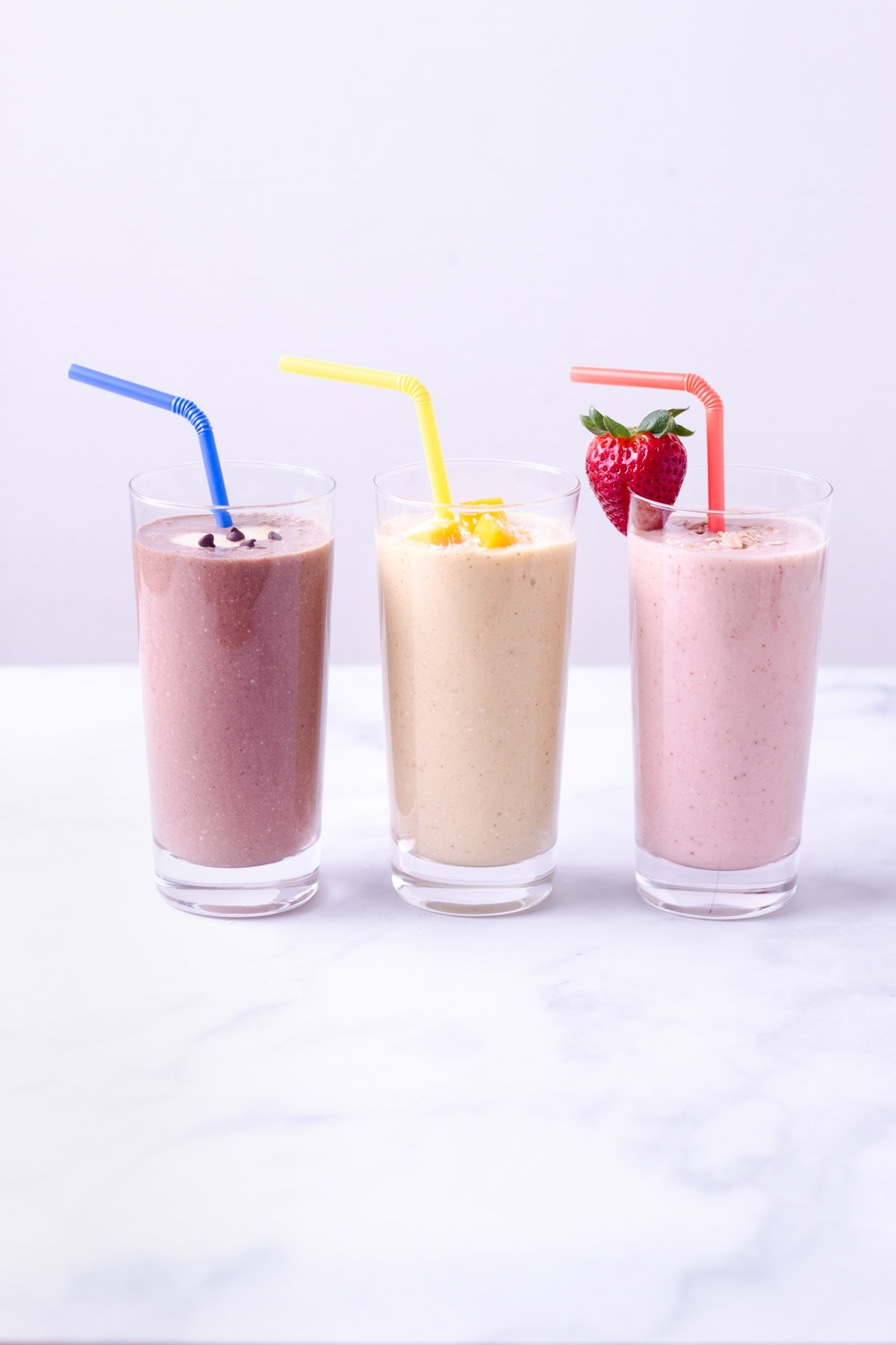 Three breakfast oatmeal smoothies lined up: chocolate, mango and strawberry.
