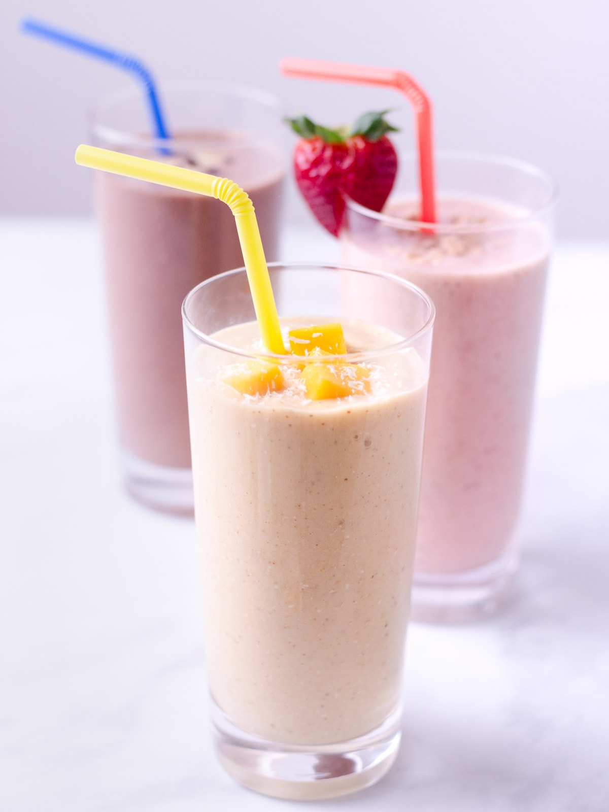 Straight on view of three oat smoothies with the mango one in the forefront, strawberry one behind and chocolate one in the back.