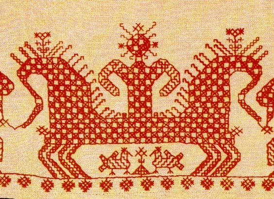 Baltic/Archangel region, hemline of a woman's underdress. The Maiden crowned with the Sun drives a chariot. Two horses are harnessed into it. A checkered pattern covering the picture symbolizes characters depicted are gods. There are birds under a horse's belly: it means the chariot flies in the sky.