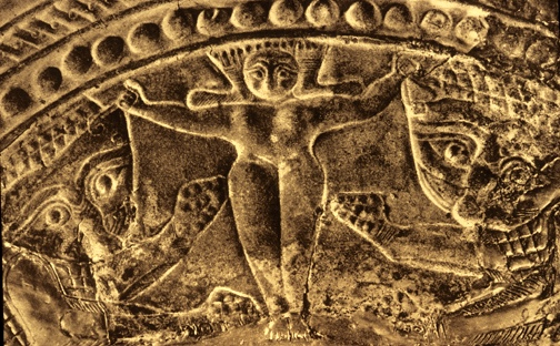Bronze shield from the Idaean Cave on Crete. The Mistress of Animals stands grasping a lion in either hand. c. 700 BCE