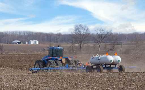 Tractor Pulling Anhydrous Ammonia Tanks Fertilizing a Farm Field_1556567969497