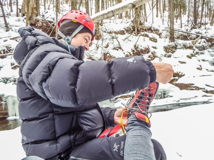 Ice Canyoning in Québec // Why You Should Be All up in This| Our guide putting my crampons on for me - ice canyoning in Québec