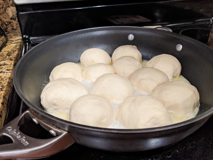 dampfnudel dumplings in a skillet on the stove