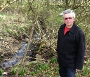 Councillor David Wilkinson at the brook