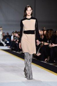 Minidress-rosa-pastello-con-maglia-nera-e-paillettes-sotto-pantaloni-a-zampa-con-pattern-a-righe-verticali