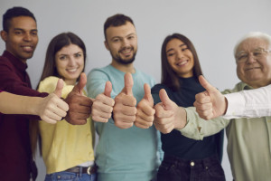 Group of happy people giving thumbs-up, approving of an idea or showing customer satisfaction
