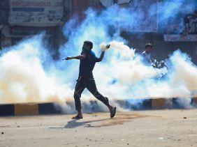 Demonstranten schleudern Tränengasbehalter auf Sicherheitskräfte in Lahore.