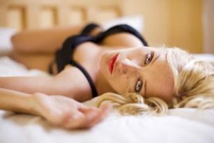 Sexy Blondine wartet im Bett