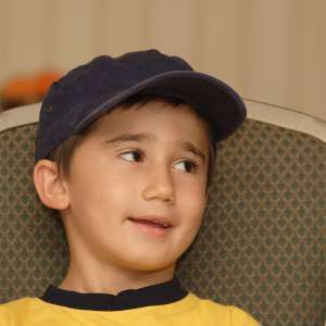 Boy with baseball cap looking to side