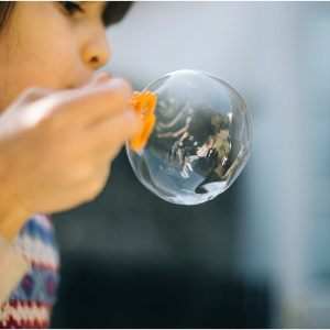 child blowing bubble
