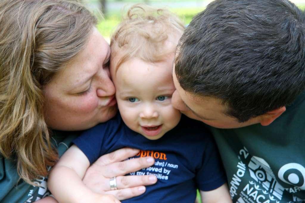 parents-kissing-little-boy