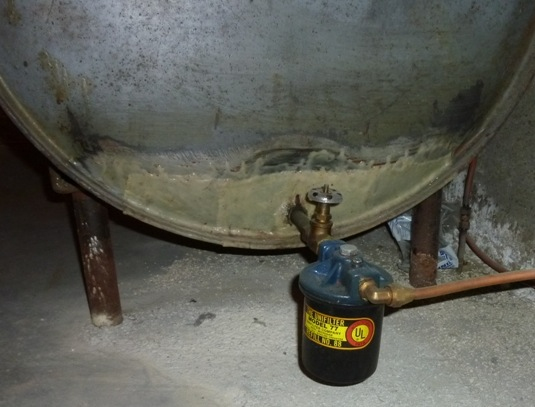 This fuel oil storage tank in a home's basement has been patched, as evidenced by the non-matching color of the tank near the valve.