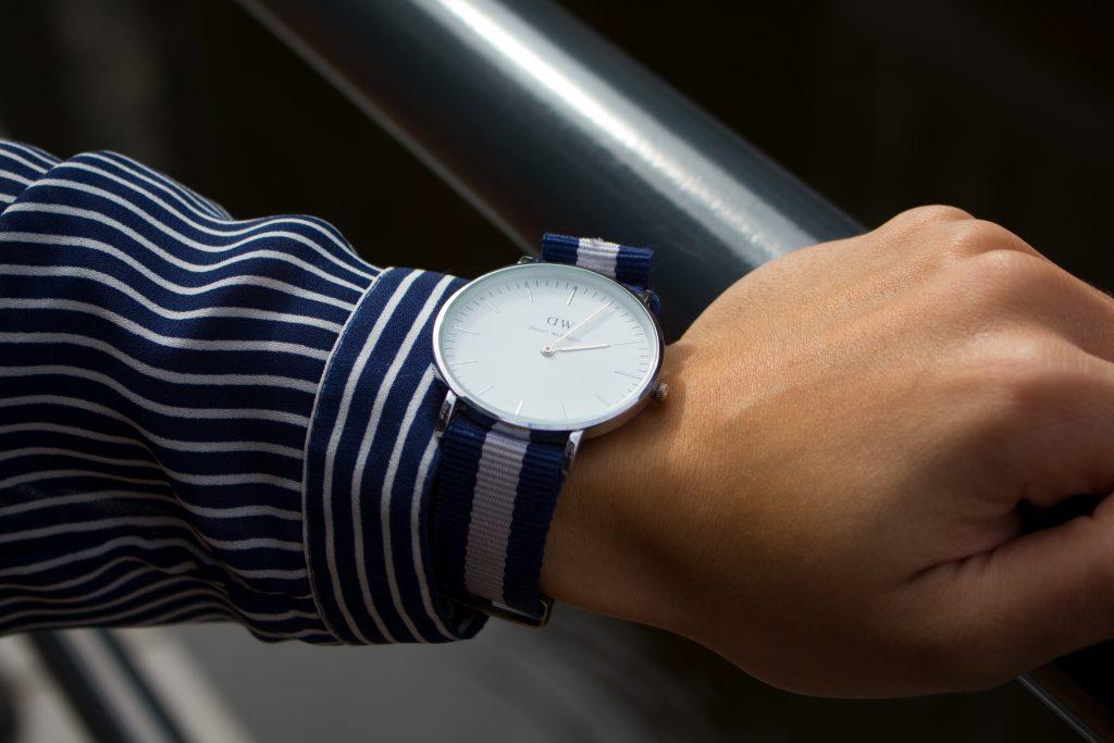 DW Classic Glasgow Horloge met zilveren klokje gefotografeerd op de reling van een brug