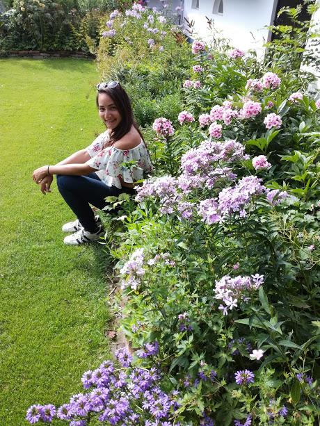 Meisje met floral offshoulder top in bloementuin