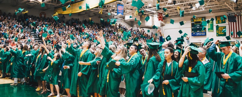 Floyd Central graduates throwing their caps in the air