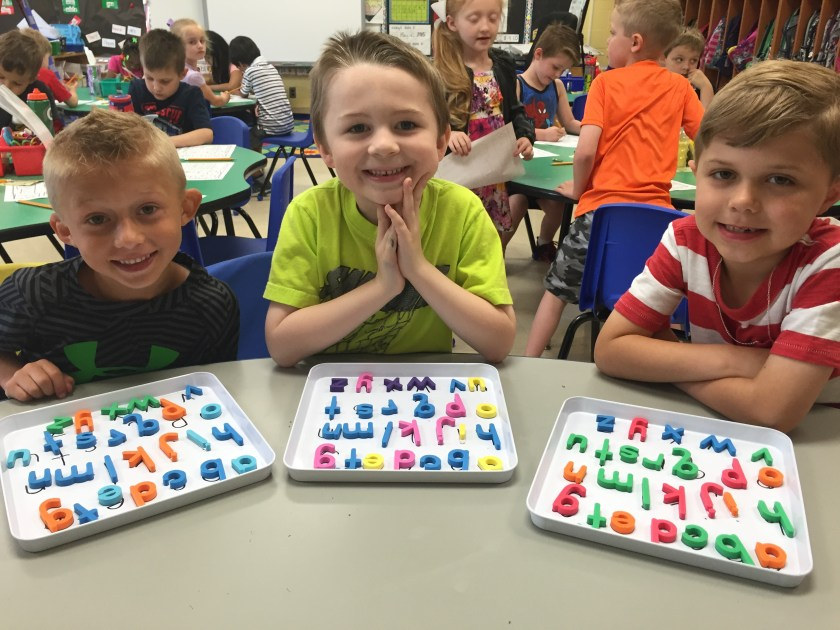 Three boys smiling while arranging magnetic letters on trays