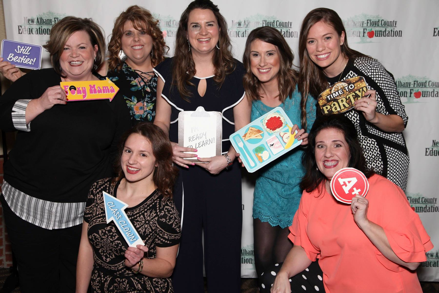 Group of teachers posing in a photo booth with education related props