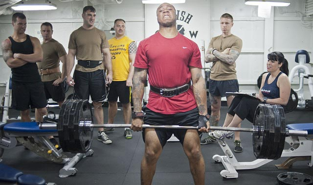 A man holding a barbel at the gym