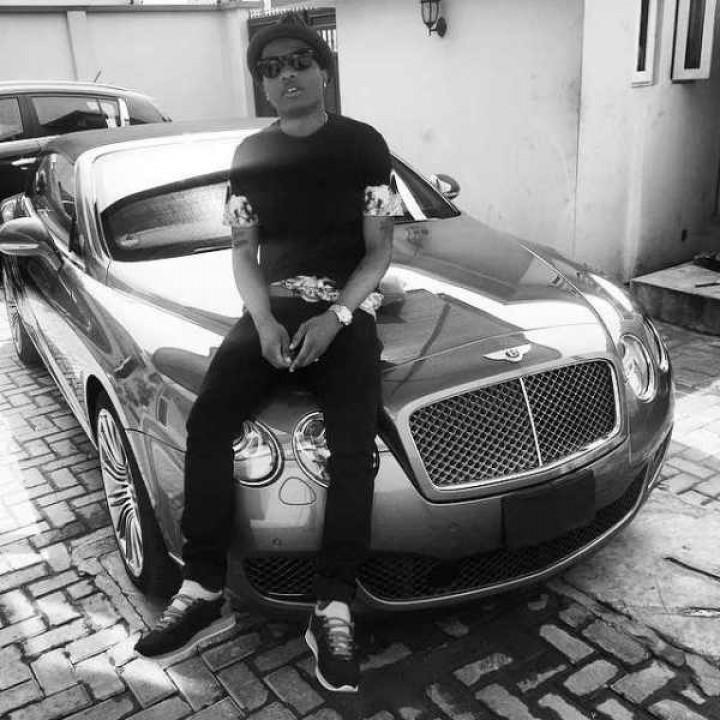Wizkid sitting on his luxurious car