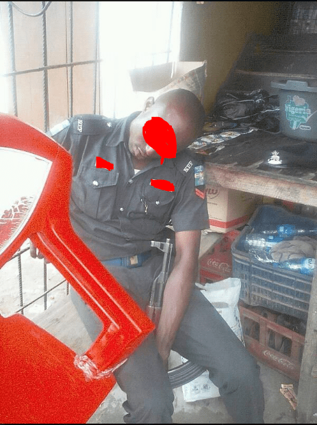 police - Nigerian Policeman Spotted Sleeping With His Rifle While On Duty (Photos)
