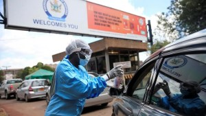 Health worker screens and disinfects visitors to prevent the spread of Covid 19 outside a hospital in Harare Zimbabwe March 26 2020 - Coronavirus: Africa And The Pandemic On Friday March 27