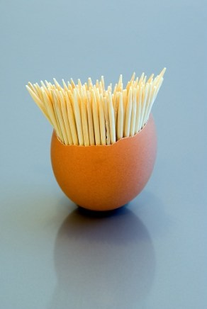 Toothpicks in eggshell on grey blue background