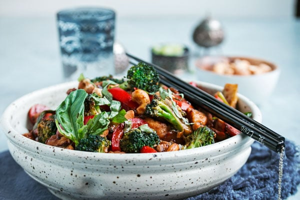 a bowl of chicken stir fry with chopsticks resting on the edge