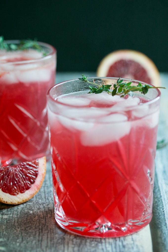 A blood orange cocktail with a piece of thyme sitting on the rim