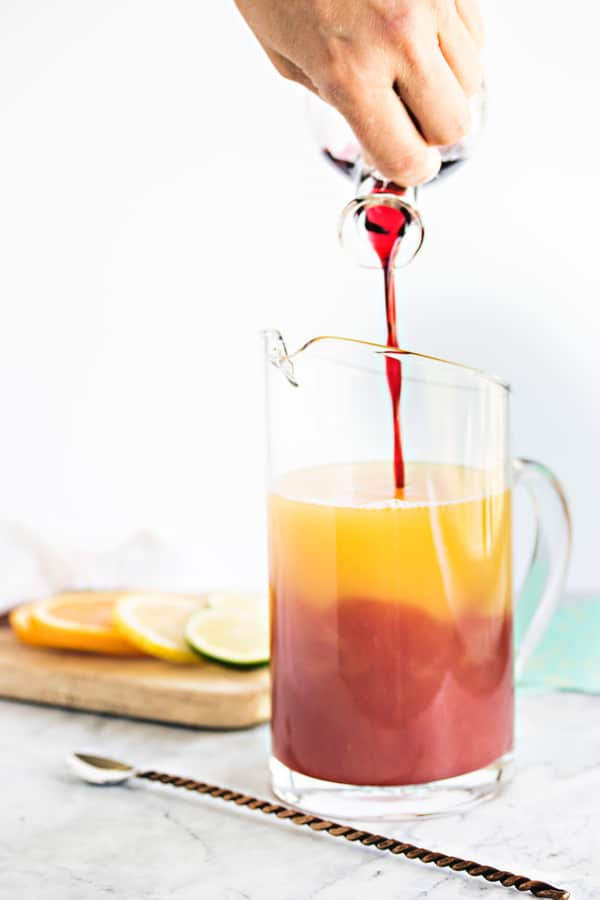pouring the hibiscus syrup into a pitcher of juice
