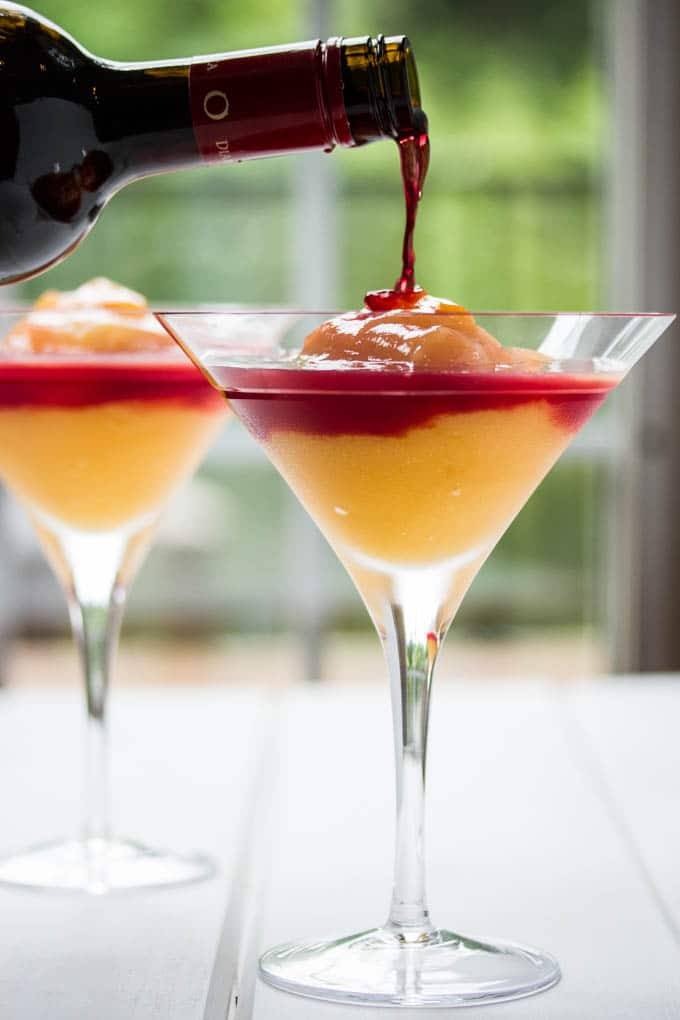 Pouring wine on top of the peach bellini cocktail