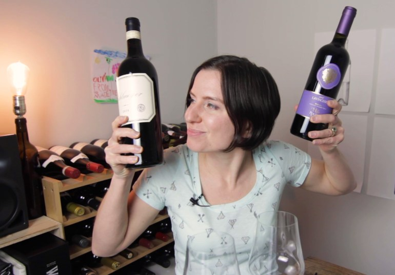 A photo of Madeline Puckette of Wine Folly March 2019 - holding 2 bottles of wine