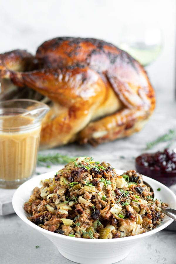 a bowl of turkey stuffing on the table with a turkey, cranberries and gravy