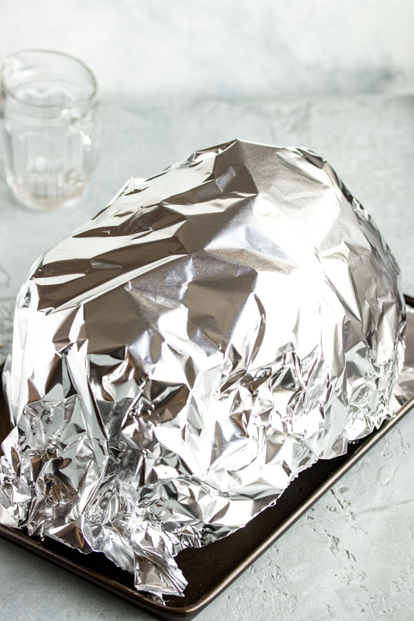 a brined turkey covered in foil to rest
