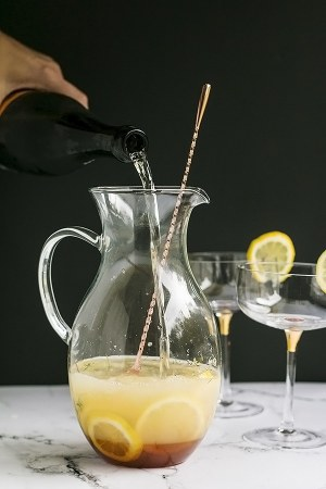 pouring the bubbly into the pitcher for the bees knees cocktail