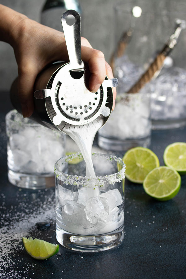 pouring a shaken margarita into a glass filled with ice