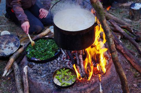 Das Bild zeigt eine freien Feuerstelle, über der mit Topf und zwei Pfannen gekocht wird. Aus einem der Töpfe steigt Dampf auf, die Pfannen beinhalten Brennesselblätter und Käse im Buchenblatt.