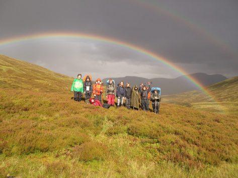 Ein Gruppenfoto von Jugendlichen auf einer Wandertour. Die Gruppe steht in weitläufigen Heidekraut. Im Hintergrund wird der Himmel von einem Regenbogen geziert, der sich über das gesamte Foto erstreckt.