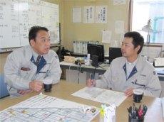 事務所内で工事の説明を受ける中山社長 (左から中山社長、遠藤所長)