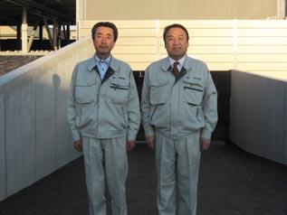 建物の前で、左から 釜山係長、中山社長