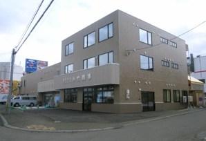 写真手前側「小竹商事」と看板のある建物が増築した部分です